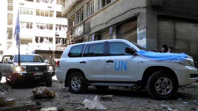 Zwei Autos der UNO fahren durch ein zerstörtes Quartier.