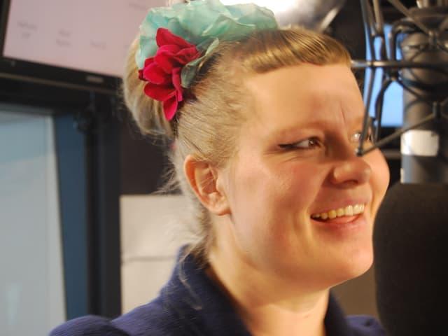 Zu sehen ist die Sängerin Nicole Bernegger. Ihre Frisur ist zu einem Dutt gebunden. Ihr Haar ziert eine rote und eine türkis-farbene Schleife.