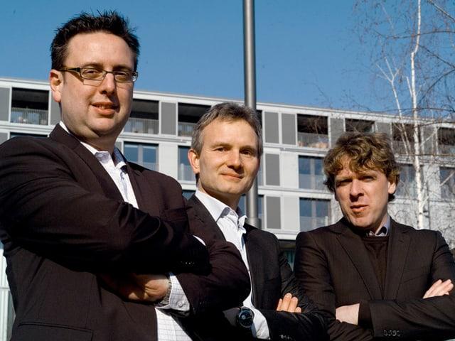 Die drei Gründer von InShero in schwarzen Anzügen und weissem Hemd mit verschränkten Armen.