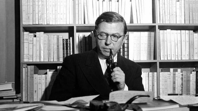 Portrait des Pfeiferauchers Sartre vor seinem Bücherregal.