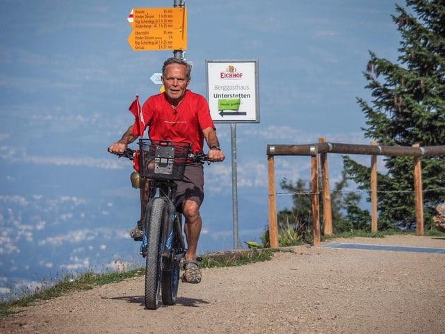 Ein Fahrradfahrer auf einer steinigen Bergstrasse.