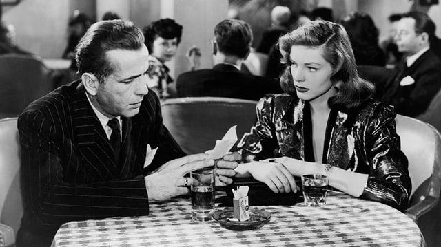 Ein Mann und eine Frau sitzen an einem Café-Tisch und lesen einen Zettel.