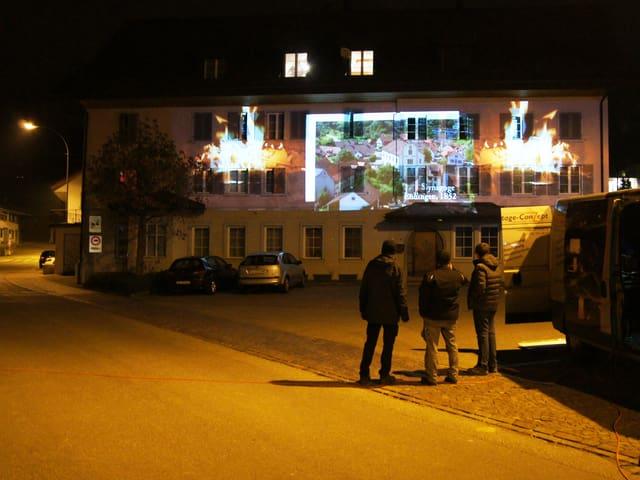 Menschen betrachten Projektion von Bildern an Hauswand.