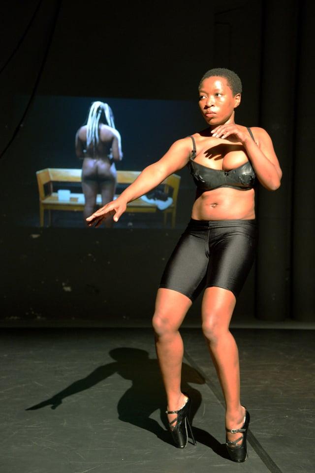 Die Tänzerin Chuma Sopotela vor einem Bild einer nackten Frau von hinten. Sie trägt schwarze Fahrradhosen, einen schwarzen BH und Schuhe, deren so hohen Absatz sie von vorne wie Ballettschuhe aussehen lassen.