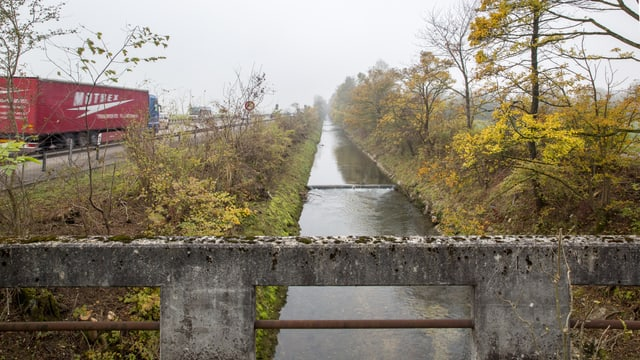 Ein Flüsschen, stark kanalisiert, daneben eine Autobahn mit einem Lastwagen.