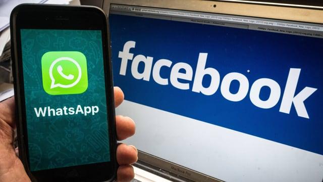 Eine Hand Hält ein Smartphone mit Whatsapp Logo vor einen Laptopbildschirm mit Facebook-Logo