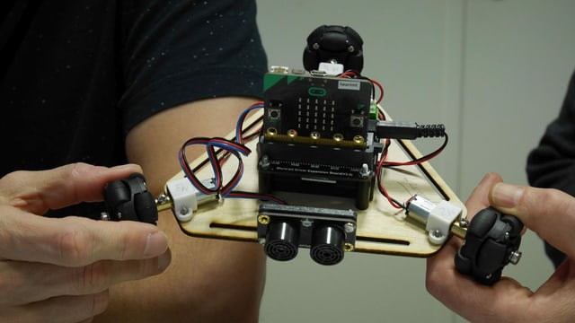 Zwei Hände halten einen kleinen Roboter.