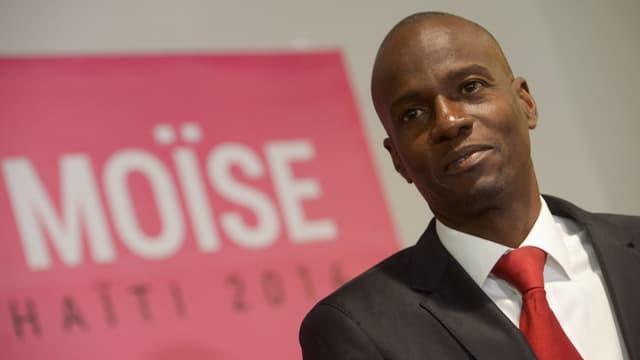 Moïse vor einem rosa Wahlplakat.