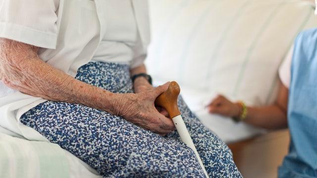 Eine alte Frau sitzt auf einem Bettrand.