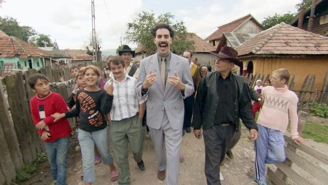 Ein Mann in grauem Anzug geht durch ein Dorf, umzingelt von weiteren Menschen.