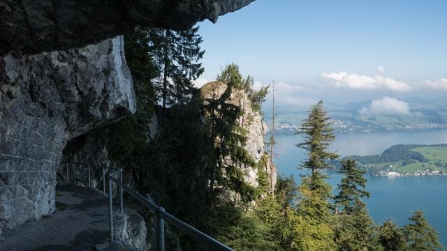 Weg der in einen Felsen gehauen ist mit Aussicht auf See und Berge.