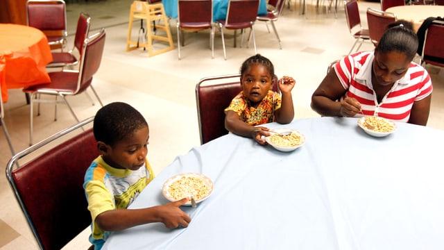 Eine Mutter isst ein Frühstück im Raum einer Kirche in Charlotte, North Carolina.