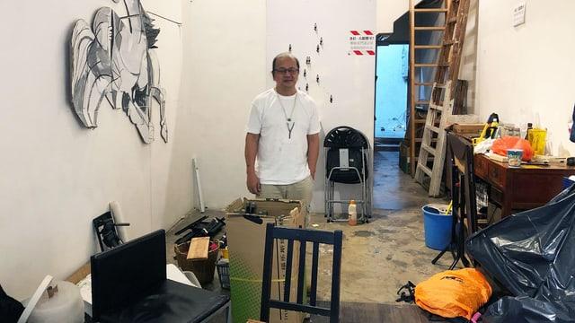 Ein Mann steht in einem Raum. Es stehen Kisten und Müllsäcke herum.