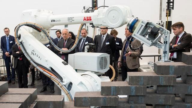 Ein Roboterarm stapelt schwarze Klötze, im Hintergrund schauen Bundesrat Schneider-Ammann und andere Männer interessiert zu.