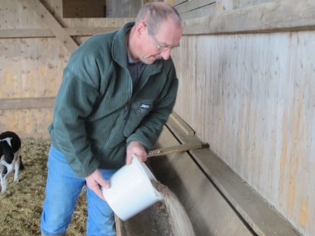 Willi Lüscher giesst Futter in einen Trog.