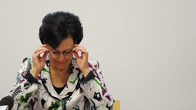 Die Zürcher Finanzdirektorin Ursula Gut fasst sich an die Brille und schaut auf ein Blatt.
