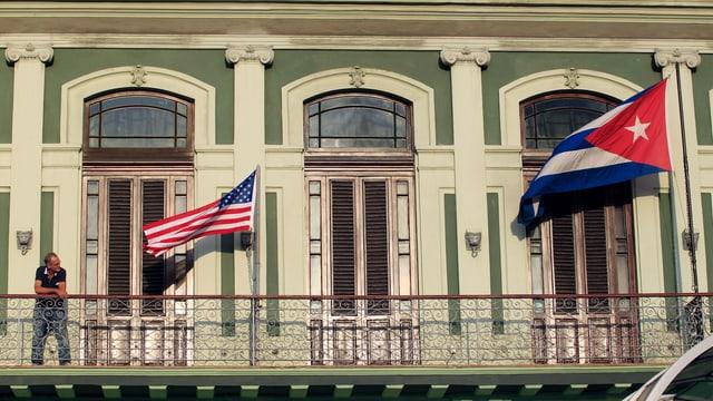 Eine USA- und eine Kubaflagge wehen an einem Gebäude in Havanna.