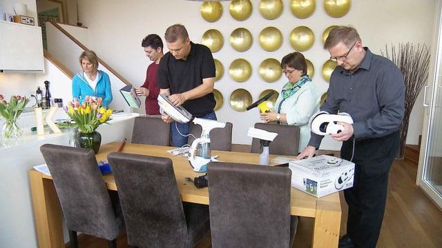 Fünf Personen stehen um einen Tisch und betrachten Fensterreinigungs-Geräte.