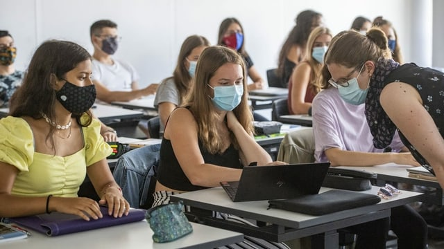 Klassenzimmer mit Schülerinnen und Schülern, die Maske tragen.