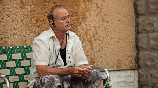 Bill Murray sitzt mit Kopfhörern auf der Bank.