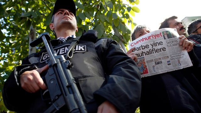 Ein Polizist mit Maschinengewehr, hinter ihm hält jemand eine Cumhuriyet-Zeitung in die Luft.