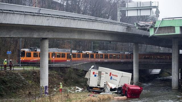 Das Wrack des Lastwagens liegt am Ufer der Sihl, darüber die Autobahnbrücken.