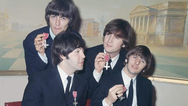 Die Beatles in schwarzen Anzügen.