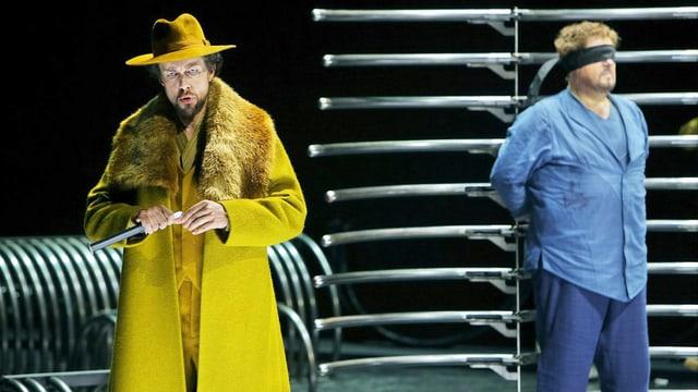 König Marke trägt einen gelben Mantel mit Fellkragen und einen gelben Hut. Tristan steht neben ihm mit verbundenen Augen.