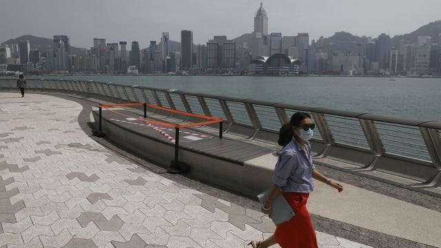 Frau mit Mundschutz läuft vor der Hongkonger Skyline