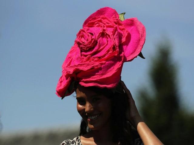 Eine Frau mit Hut in der Rorm einer Rosenblüte.