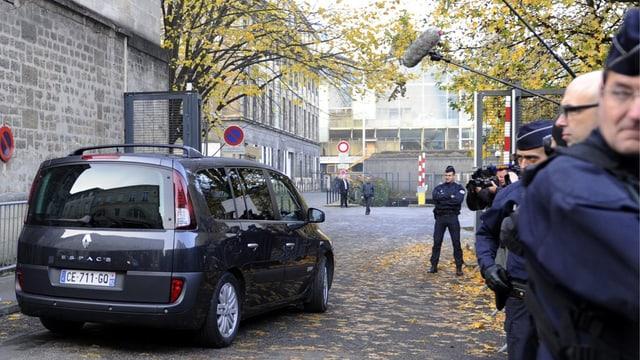 Grosser schwarzer Citroen vor einer Absperrung, überall Sicherheitsleute.