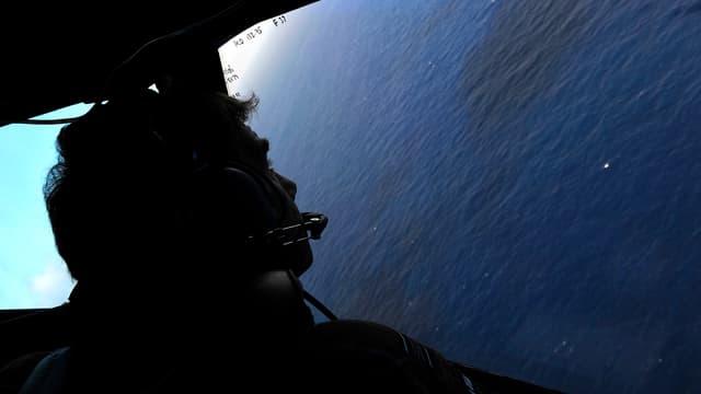 Mann aus Flugzeugfenster auf das Meer blickend