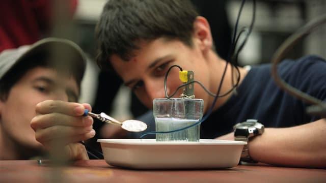 Zwei Gymnasiasten bei einem Experiment im Chemieunterricht.