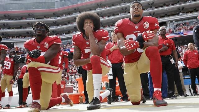 drei schwarze Footballspieler knien.