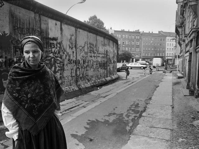 Frau mit Kopftuch vor der Mauer in Kreuzberg 1988