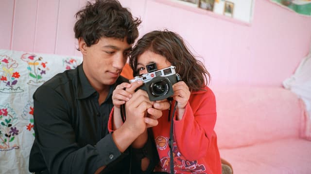 Flüchtlingskinder auf Sofa mit einer Fotokamera.