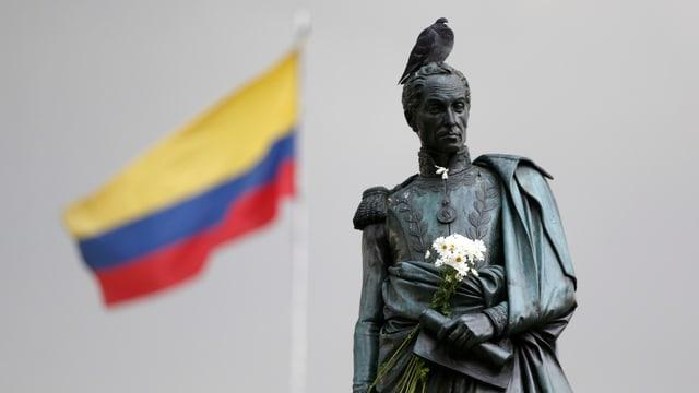 Die Statue des Freiheitskämpfers Simon Bolivar mit einer Friedenstaube auf dem Kopf und im Hintergrund flattert die kolumbianische Flagge.