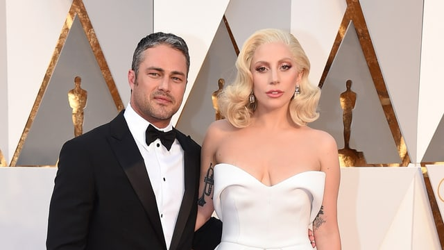 Freund Taylor Kinney steht im Smoking neben Lady Gaga im weissen Kleid bei den Oscar-Verleihungen.