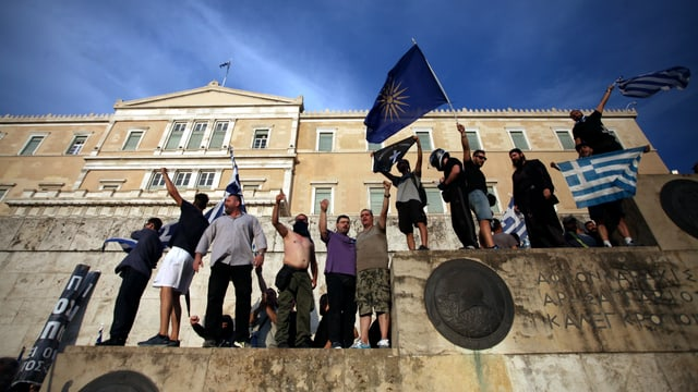 Männer stehen mit Flaggen vor dem griechischen Parlamentsgebäude