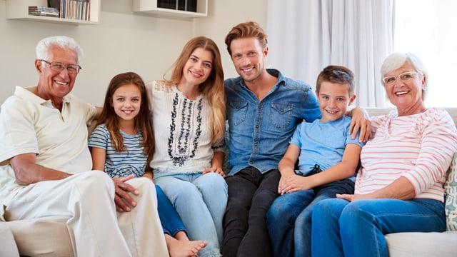 Grosseltern, Eltern und Kinder sitzen auf dem Sofa.