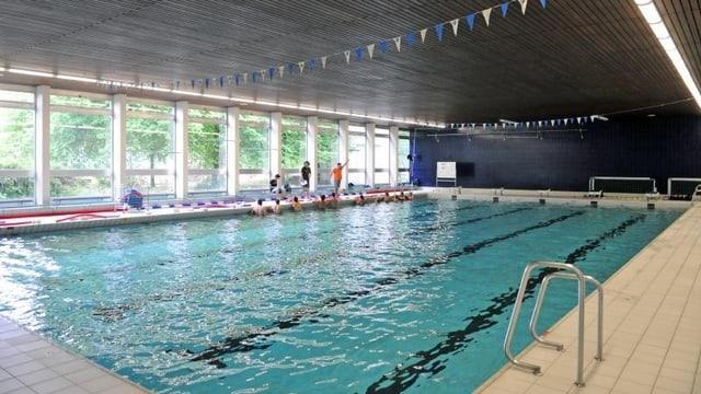 Ein Gruppe Schwimmer hört in der St.-Jakobshalle den Instruktionen eines Schwimmtrainers zu