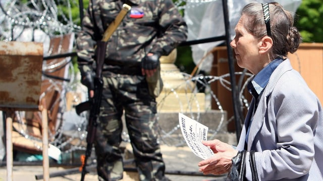 Eine Frau läuft mit einem Zettel in der Hand vor einem bewaffneten Mann vorbei.