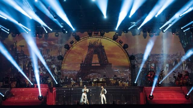 Ein Mann und eine Frau stehen auf einer Konzertbühne, von der aus zahlreiche Scheinwerfer in die Luft strahlen.