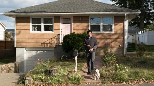 Paterson steht mit Hund vor seinem Haus.