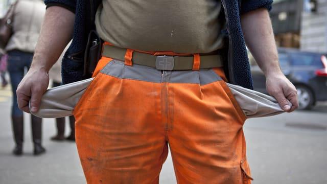 Ein Bauarbeiter zeigt seine leeren Hosentaschen.