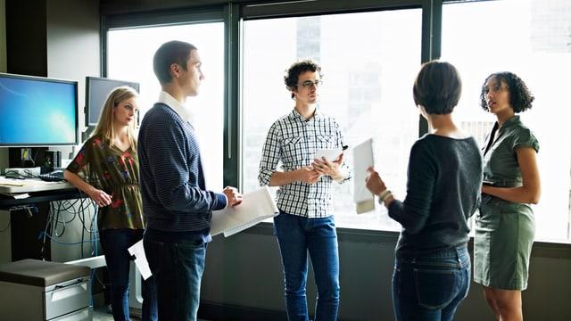 Drei Frauen und zwei Männer stehen in einem Büro in einem Kreis für eine Besprechung.