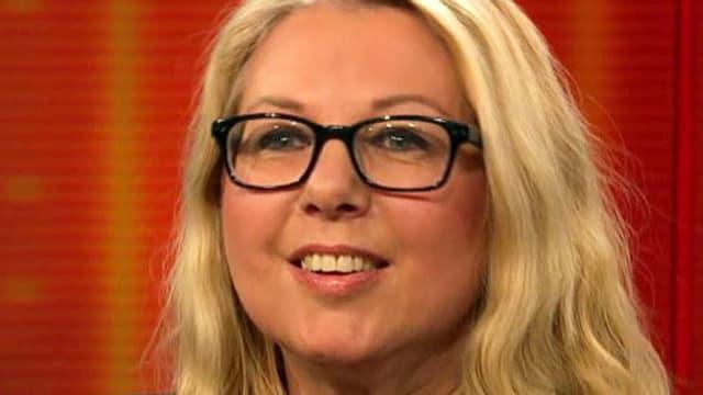 Nahaufnahme mit blondem Haar und schwarzer, eckiger Brille.