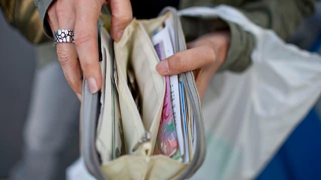Eine Frau hält ihr Portemonnaie geöffnet.