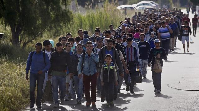Eine lange Menschenkolonne marschiert auf einer Strasse. Es sind vorwiegend Männer.
