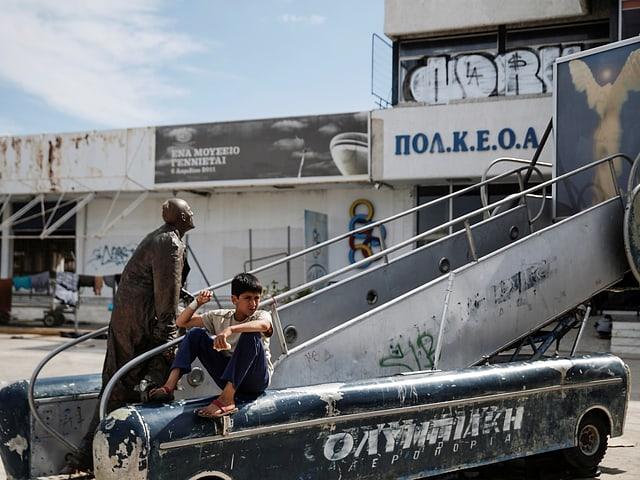 Ein Junge sitzt neben einer Statue auf einem alten Gangway auf Athens stillgelegtem Flughafen.